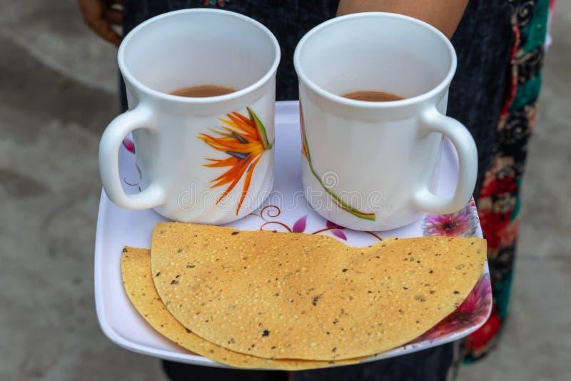 Tè con papad, donna che serve tè indiano fotografie stock libere da diritti