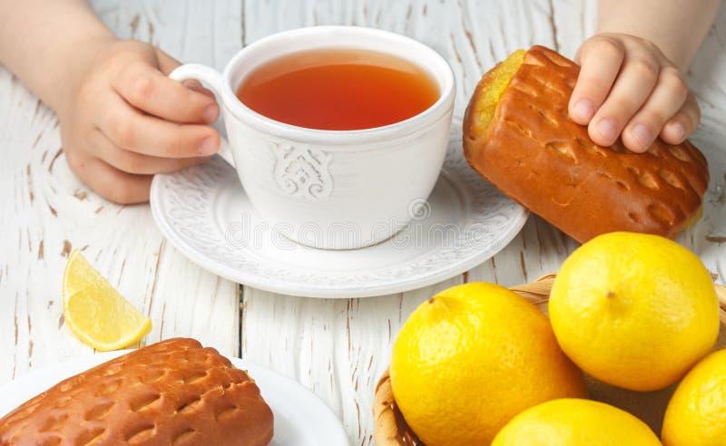 Tè del bambino della prima colazione e panini casalinghi freschi con il materiale da otturazione del limone fotografia stock