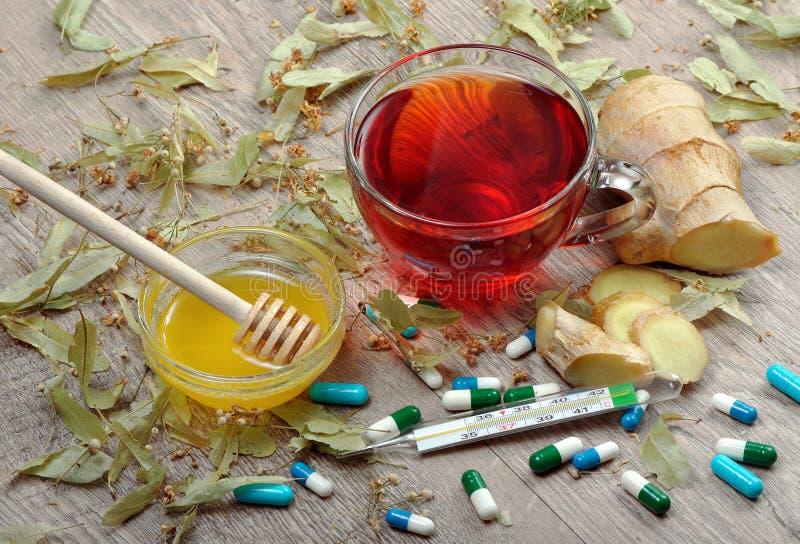 Tè del tiglio sulla tavola di legno una tazza del tè, del miele, dello zenzero, del termometro e delle compresse del tiglio rimed immagini stock libere da diritti