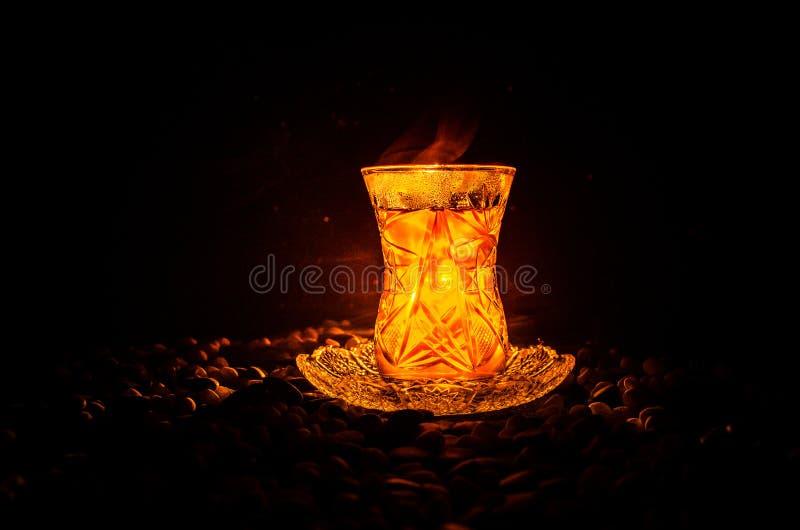 Tè dell'Azerbaigian del turco nel glasse tradizionale e vaso su fondo nero con le luci ed il fumo Tazza tradizionale di Armudu fotografia stock libera da diritti