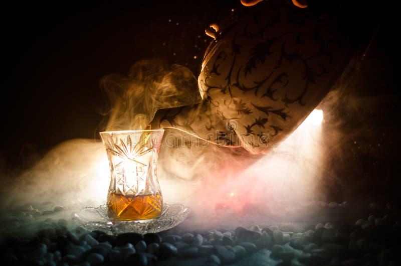 Tè dell'Azerbaigian del turco nel glasse tradizionale e vaso su fondo nero con le luci ed il fumo Tazza tradizionale di Armudu fotografia stock