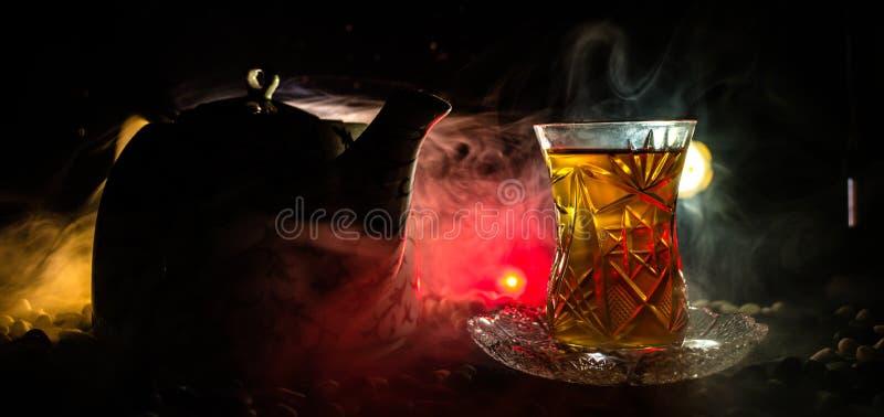 Tè dell'Azerbaigian del turco nel glasse tradizionale e vaso su fondo nero con le luci ed il fumo Tazza tradizionale di Armudu immagini stock