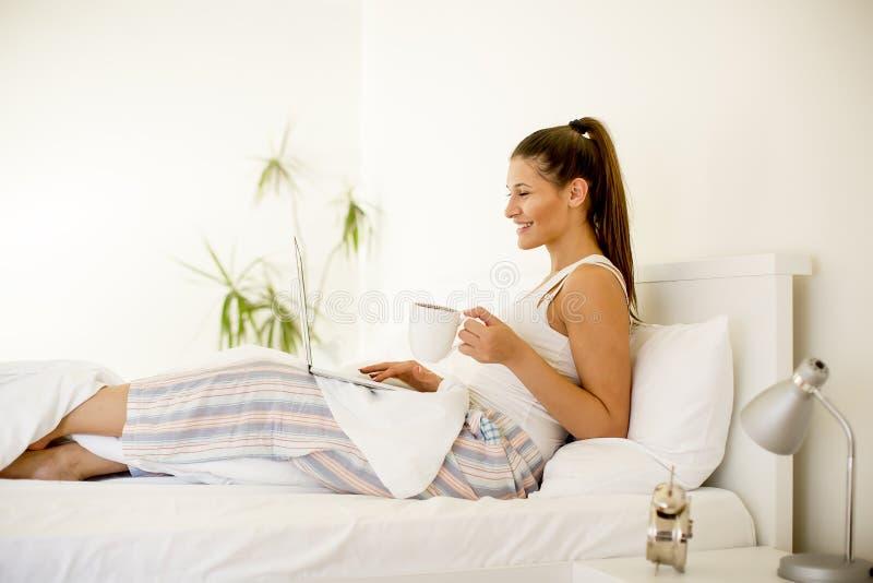 Tè della donna o caffè ed usando computer portatile beventi a letto a fotografie stock