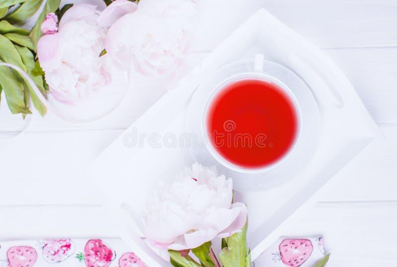 Tè della frutta e peonie rosa dei fiori su fondo di legno bianco Vista superiore immagini stock