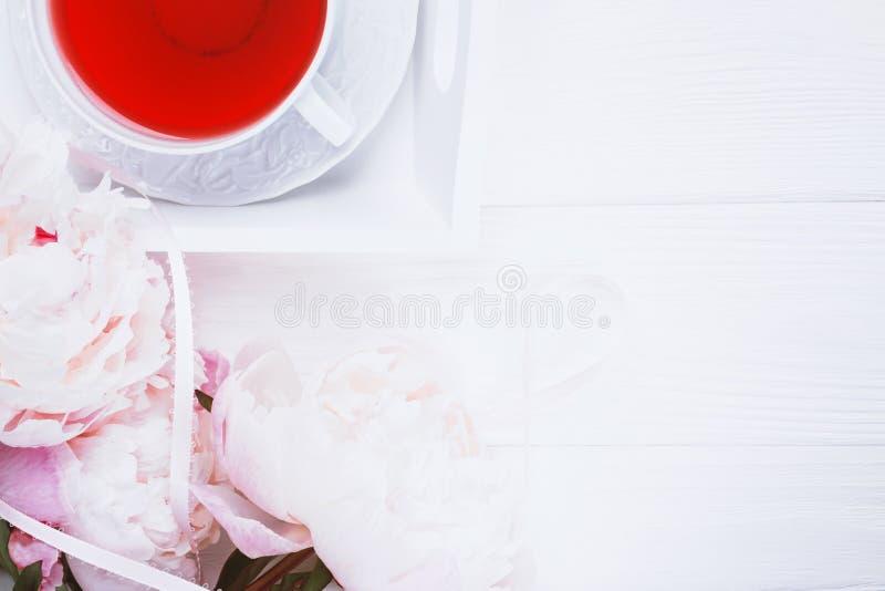 Tè della frutta e peonie rosa dei fiori su fondo di legno bianco Vista superiore fotografia stock libera da diritti