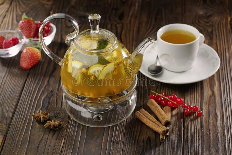 Tè della frutta in teiera di vetro e tazza bianca su fondo di legno con le bacche fresche immagine stock libera da diritti