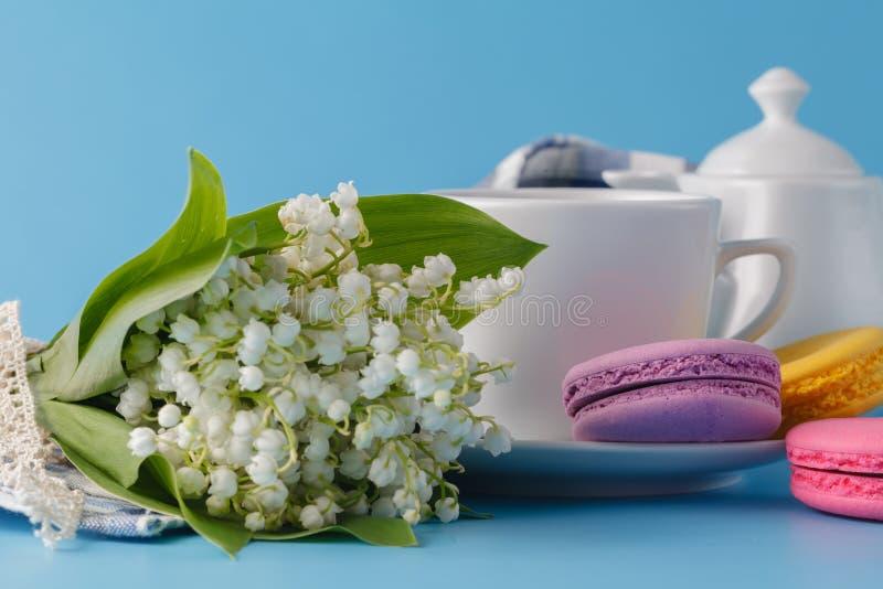 Tè della primavera che beve con i fiori bianchi su fondo blu fotografia stock libera da diritti