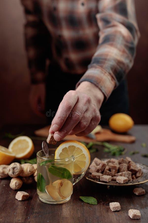 Tè dello zenzero con zucchero bruno, il limone e la menta sulla vecchia tavola di legno fotografie stock