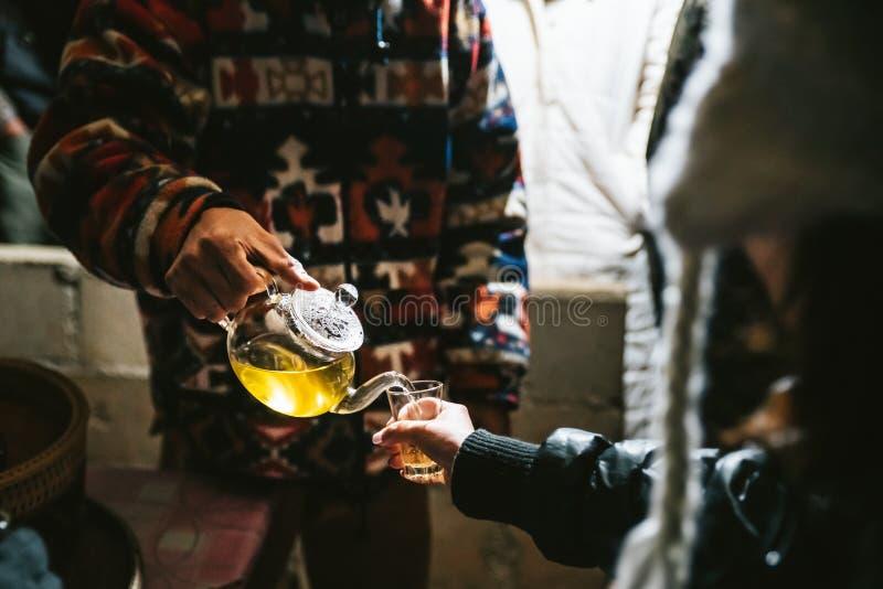 Tè di camomilla caldo di Pouring di barista dalla teiera a bicchiere per il tester nel villaggio di Akha di Maejantai sulla colli immagini stock