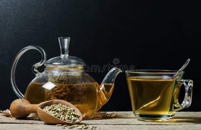 Tè di erbe del finocchio di infusione in tazza di vetro con i semi di finocchio secchi in pala di legno immagini stock