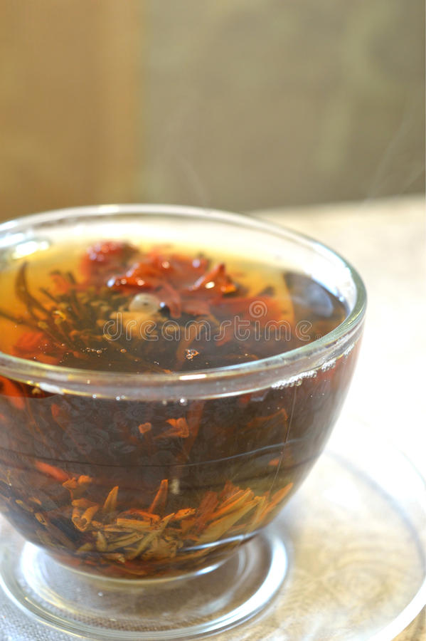 Tè di fioritura nella tazza trasparente sul piattino trasparente, il vapore dal tè caldo fotografia stock