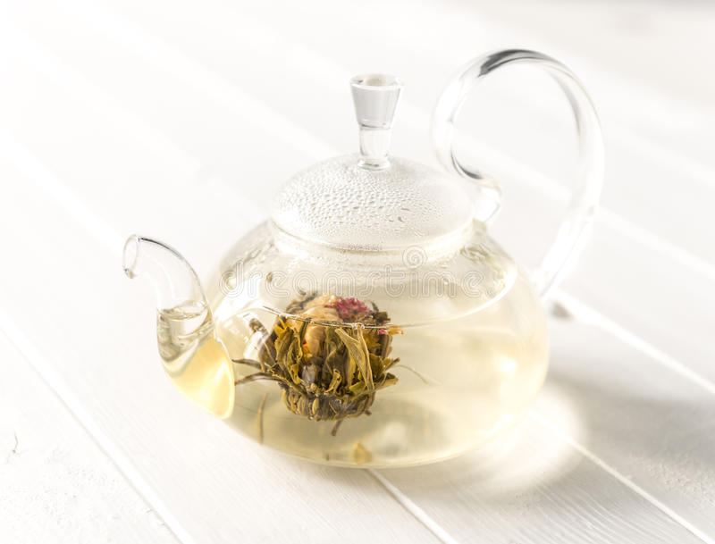 Tè di fioritura o sbocciante in teiera di vetro immagini stock
