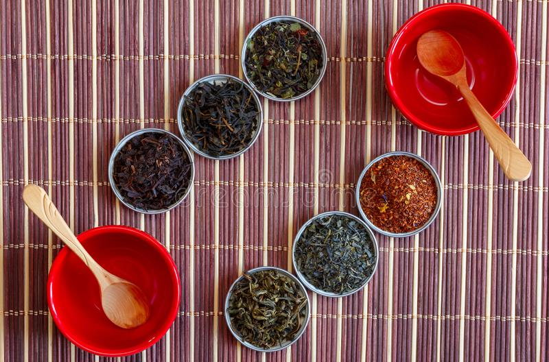 Tè di Ivan, rooibos Marrakesh, tè nero, tè verde e cucchiai di legno in ciotole rosse su una stuoia di bambù marrone, vista super immagini stock