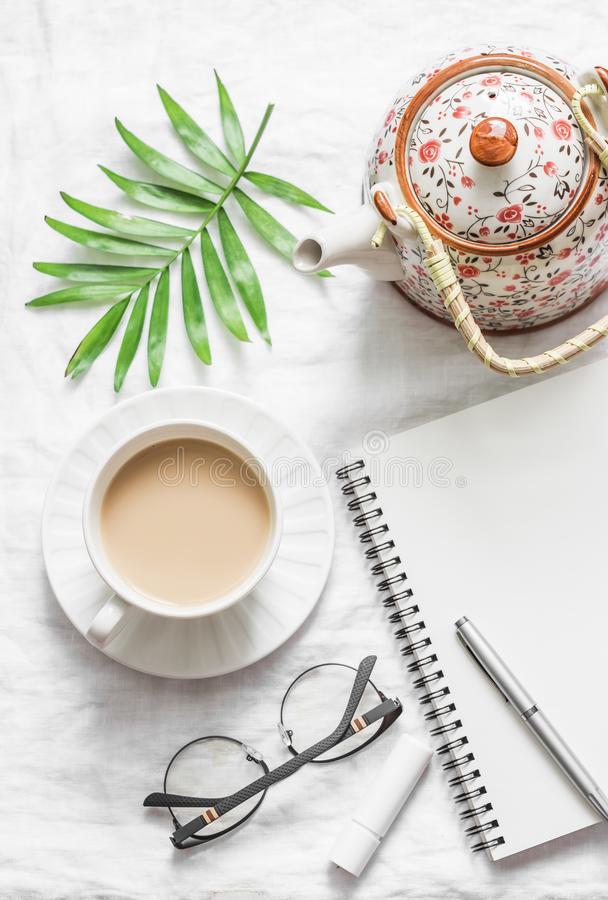Tè di Masala, teiera, blocco note, vetri, penna, foglia verde del fiore su fondo bianco, vista superiore Pianificazione di ispira immagine stock