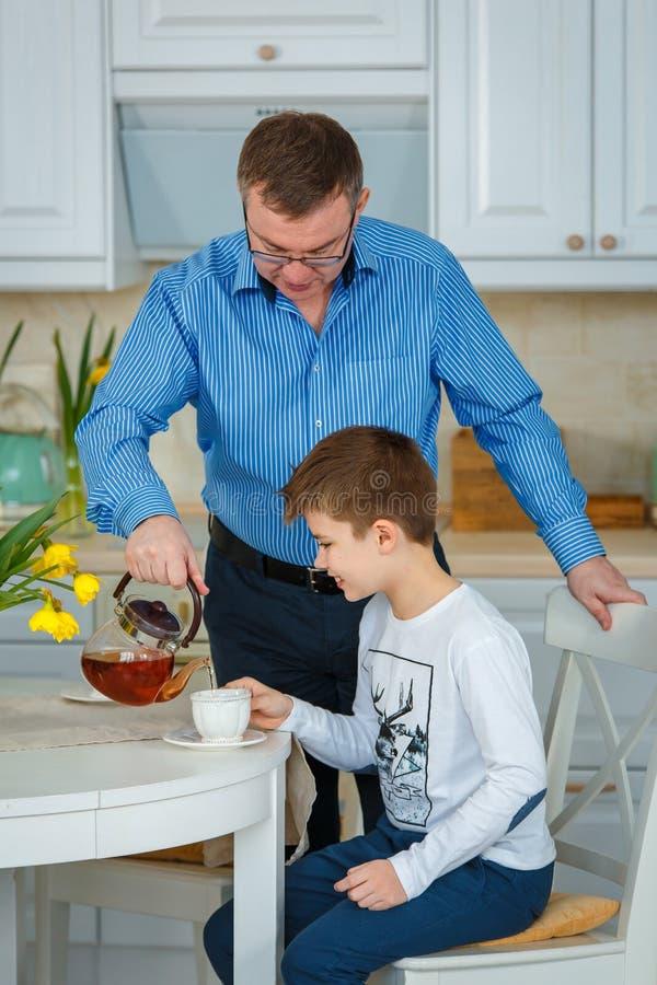 Tè di mattina Il padre versa il tè immagini stock libere da diritti