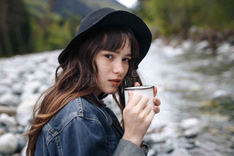 Tè di versamento o caffè del viaggiatore irriconoscibile da foggiare a coppa dal termos sul fondo della cascata Concetto di viagg immagini stock libere da diritti