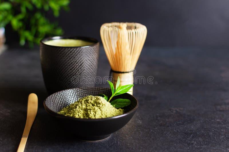 Tè e accessori per tè di colore verde biologico su fondo nero concetto di cerimonia del tè giapponese fotografia stock libera da diritti