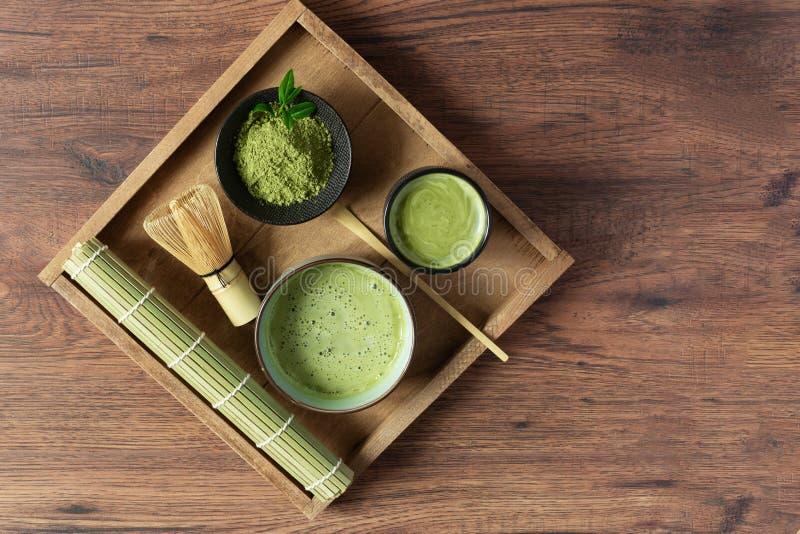 Tè e accessori per tè di colore verde biologico su vassoio in vista superiore di una tavola di legno concetto di cerimonia del tè fotografie stock libere da diritti