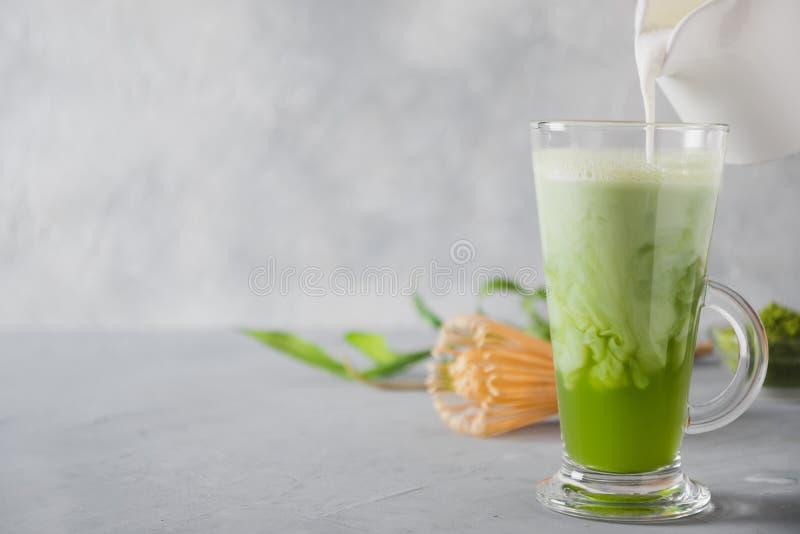 Tè e latte verdi di matcha in vetro del latte sulla tavola grigia Vista superiore Spazio per testo fotografie stock libere da diritti