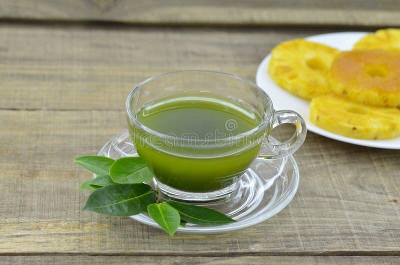 Tè fresco di matcha in tazza con l'inceppamento dell'ananas sulla tavola di legno immagine stock