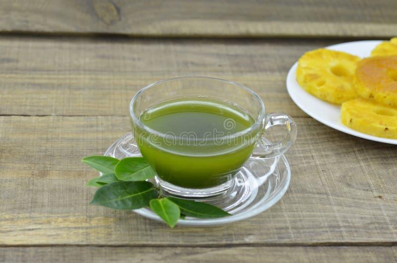 Tè fresco di matcha in tazza con l'inceppamento dell'ananas sulla tavola di legno fotografia stock