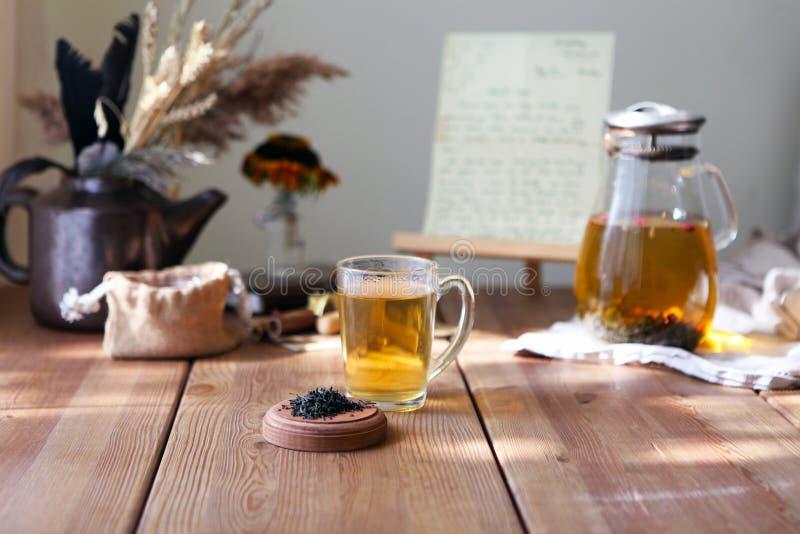 Tè heral tradizionale con la teiera di vetro, tazza, germogli rosa secchi Fiori sulla tavola di legno a casa, fondo di luce solar immagini stock libere da diritti