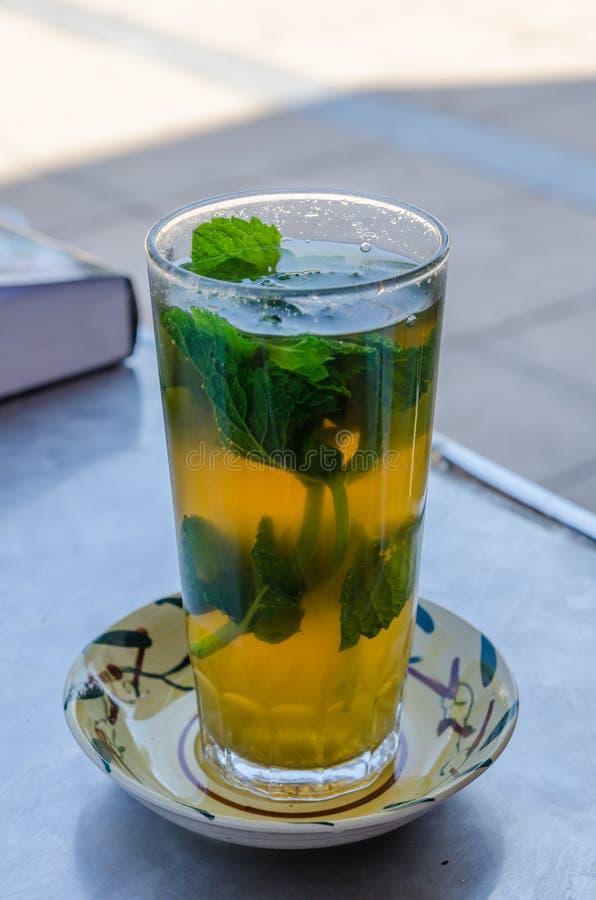 Tè marocchino dolce tradizionale con le foglie di menta in vetro alto sulla tavola esterna, Marocco, Nord Africa fotografia stock libera da diritti