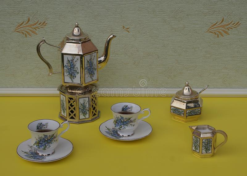 Tè per due, tazza da the inglesi, piattini, teiera placcata in argento su una stufa d'argento, brocca crema, ciotola di zucchero  fotografia stock