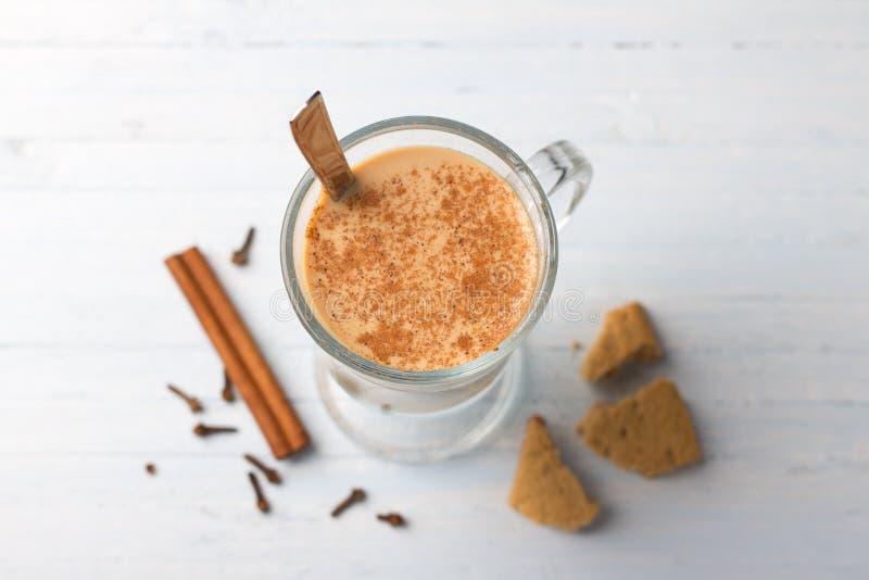 Tè piccante riscaldato con latte in una tazza di vetro e bastoncini di cannella, cloves, con biscotto di pan di zenzero fotografia stock