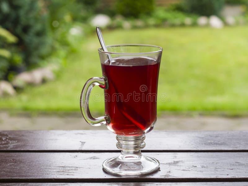 Tè rosso della frutta in tazza di vetro con il cucchiaio sulla tavola di legno, fondo del bokeh, fuoco selettivo, DOF basso fotografia stock
