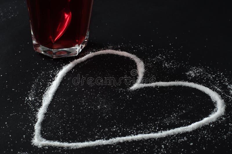 Tè rosso delle bacche in vetro e zucchero rovesciato nella forma di cuore immagine stock libera da diritti