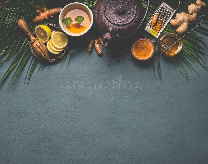 Tè sano della spezia della curcuma con il limone, lo zenzero ed il miele su fondo scuro Rimedio d'amplificazione immune fotografia stock libera da diritti