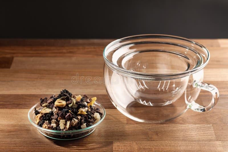 Tè sciolto e tazza di tè di vetro vuota immagine stock libera da diritti