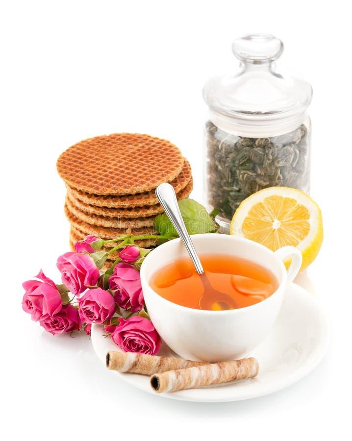Tè in tazza con i biscotti e le rose del mazzo fotografie stock