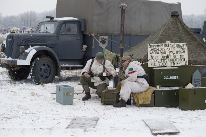Tè tedesco della bevanda dei soldati nel campo Frammento della ricostruzione militare-storica delle battaglie per la liberazione  fotografia stock
