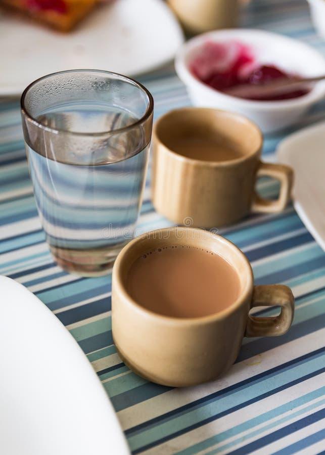 Tè tibetano del latte con un bicchiere d'acqua in hotel a Lachen Il Sikkim del nord, India fotografia stock libera da diritti