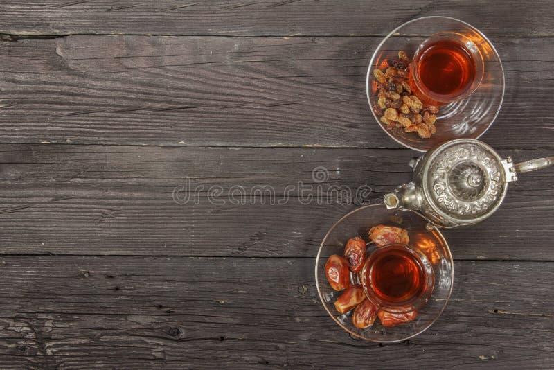 Tè tradizionale del turco e dell'arabo del Ramadan con i datteri secchi ed uva passa su una tavola nera di legno ramadan Tè fresc immagini stock libere da diritti