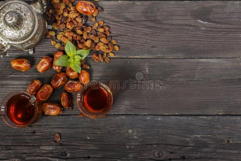 Tè tradizionale del turco e dell'arabo del Ramadan con i datteri secchi ed uva passa su una tavola nera di legno ramadan Tè fresc immagine stock libera da diritti