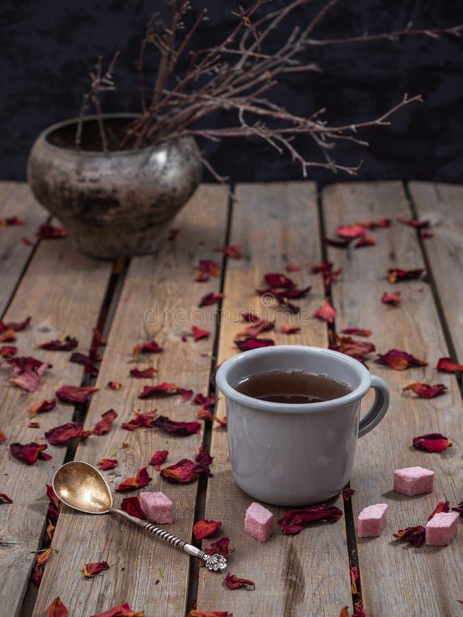 Tè in una tazza di alluminio su un fondo di legno della plancia Nei precedenti, un vaso della ghisa con i rami asciutti immagine stock