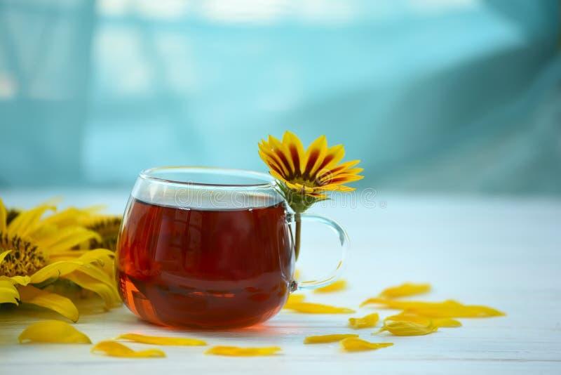 Tè in una tazza di vetro su un fondo di legno e sui fiori gialli intorno fotografie stock