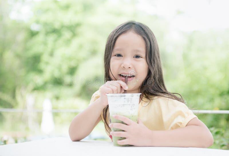 Tè verde bevente del latte ghiacciato della ragazza asiatica sveglia fotografia stock