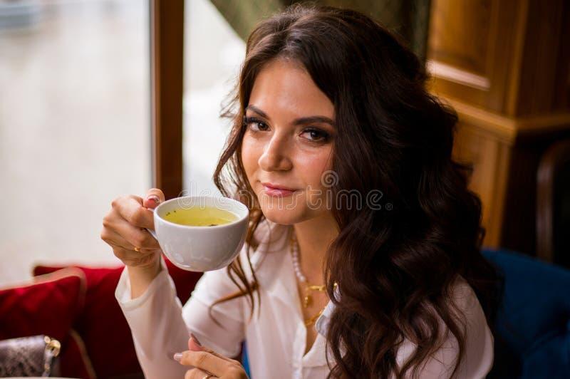 Tè verde bevente della bella donna castana in caffè della città e sguardi alla macchina fotografica immagini stock libere da diritti