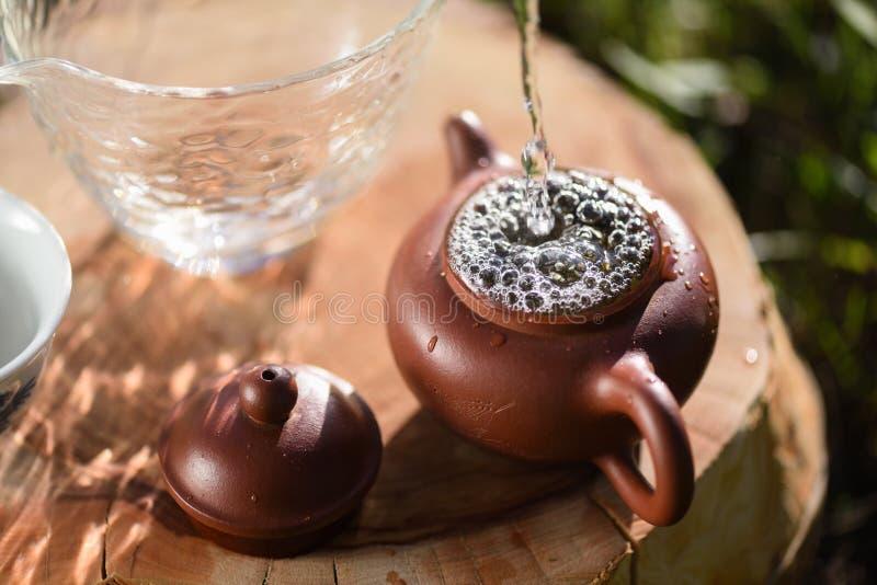 Tè verde cinese fatto Innaffi il versamento nella teiera piccola o dell'argilla immagini stock libere da diritti