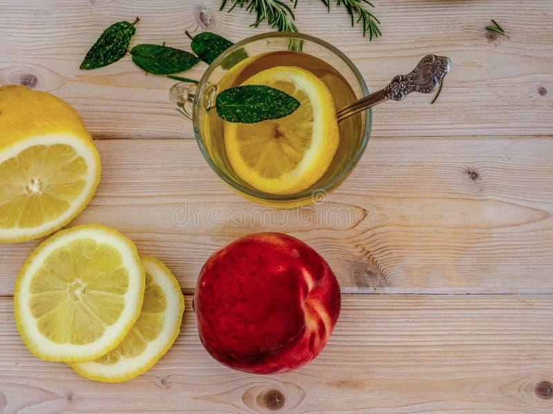 Tè verde di vetro della tazza con la menta ed il limone su una tavola Pesca colta Vista superiore immagine stock libera da diritti