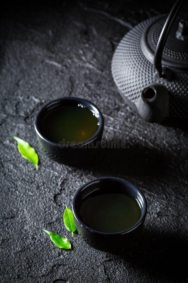 Tè verde fresco in tazza da the su roccia immagini stock libere da diritti