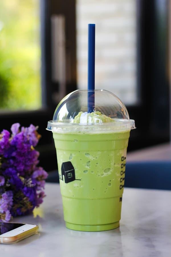 Tè verde mescolato in un vetro di plastica immagini stock