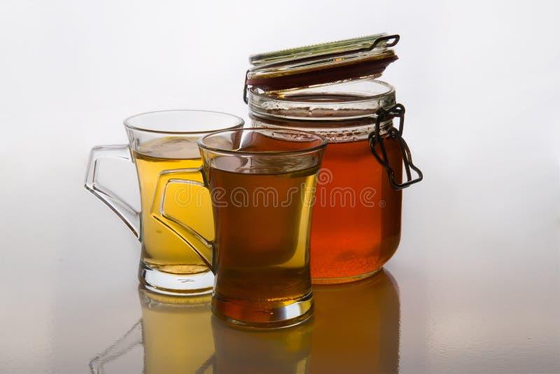 Tè verde in tazze di vetro con miele ed il limone su fondo bianco con la menta immagine stock