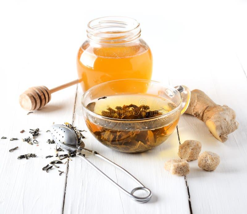 Tè verde in un piatto, in uno zucchero, in uno zenzero ed in un miele di vetro su fondo bianco fotografia stock