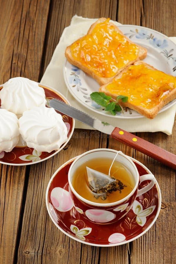 Tè verde, zefir e pani tostati con la marmellata di arance sulla parte posteriore di legno fotografia stock libera da diritti