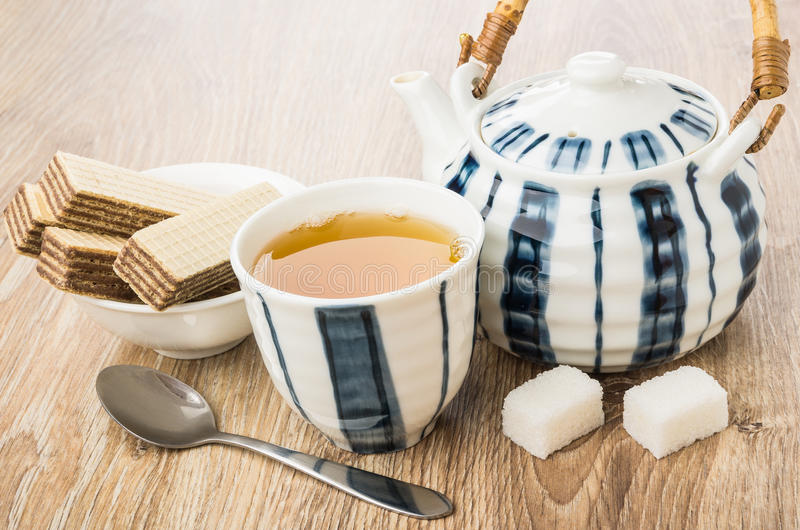 Tè, wafer in ciotola, teiera, zucchero grumoso e cucchiaio immagine stock